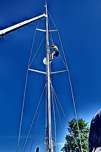 Ben going up the mast to secure the attachment points for the crane to remove the mast.